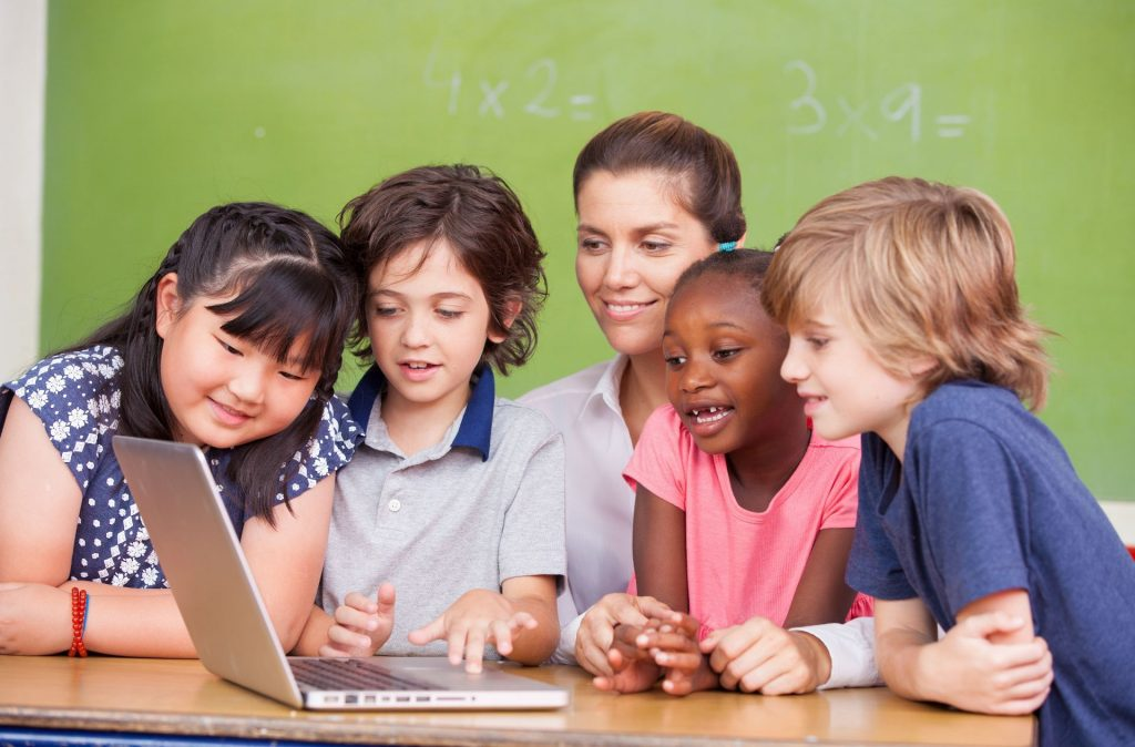 Students and teachers collaborating around a computer
