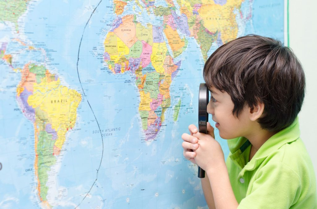 Boy looking at world map with magnifying glass Edublogs